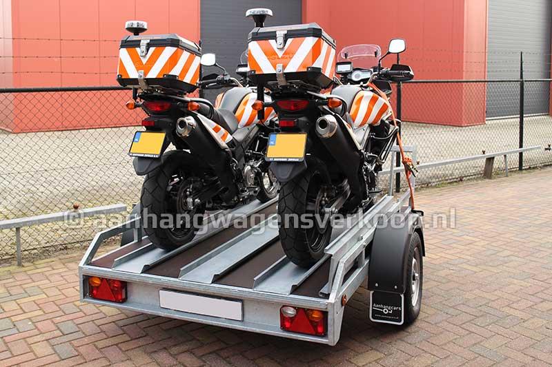 Motortransporter met twee motoren in rijgoten op de laadvloer